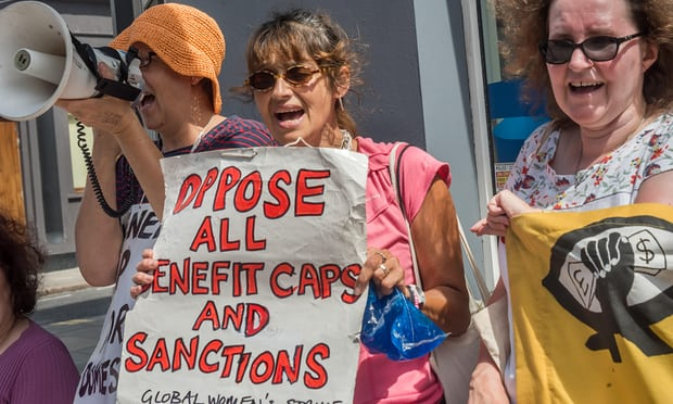 Image of three women protesting outside a building