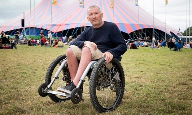 Image of man in wheelchair in a field in front of a tent.